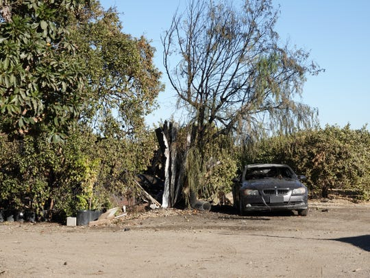 A burned-out car sits next to wreckage left by a trailer fire early Sunday outside Santa Paula, as seen from Willard Road. A teenage boy died in the blaze, authorities said.