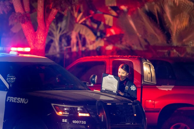 Officer Estrada works from the hood of her car as Fresno Police investigate a shooting in the 5300 block of East Lamona Avenue on Sunday, November 17, 2019. The shooting happened about 6 p.m. in east-central Fresno and left four dead and six wounded during a gathering of about 35 people to watch football in the backyard.