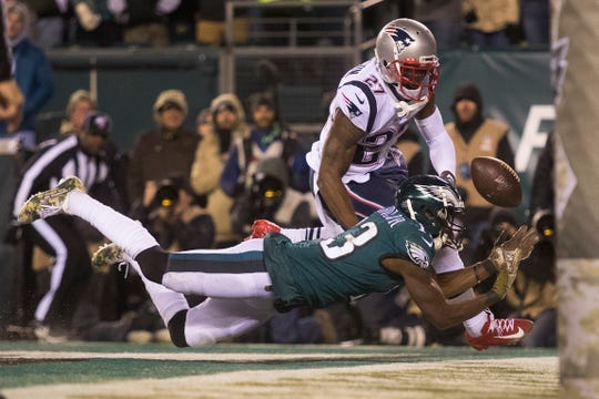 Eagles' Nelson Agholor (13) fails to bring in a pass in the end zone while guarded by New England's J.C. Jackson (27) Sunday night.