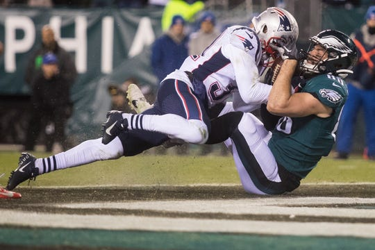 Eagles' Dallas Goedert (88) struggles with New England's Devin McCourty (32) over possession of the ball in the end zone Sunday night.
