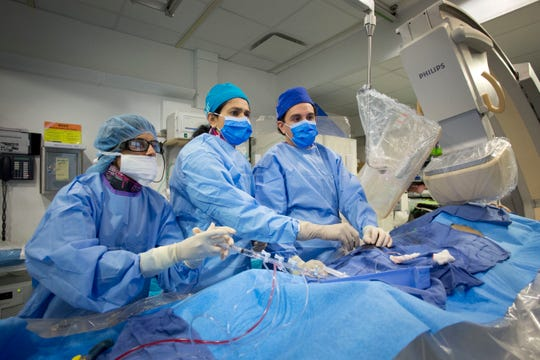 Dr. Annapoorna Kini, center, performs a non-emergency angioplasty at Mount Sinai Hospital in New York on Feb. 16, 2017. Through a blood vessel in the groin, she guides a tube to a blockage in the heart. She inflates a tiny balloon to flatten the clog, and leaves behind a mesh tube called a stent to prop the artery open.
