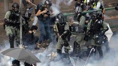 Riot police detain protesters amid clouds of tear gas at the Hong Kong Polytechnic University in Hong Kong, Monday, Nov. 18, 2019.