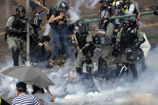 Riot police detain protesters amid clouds of tear gas at the Hong Kong Polytechnic University in Hong Kong.
