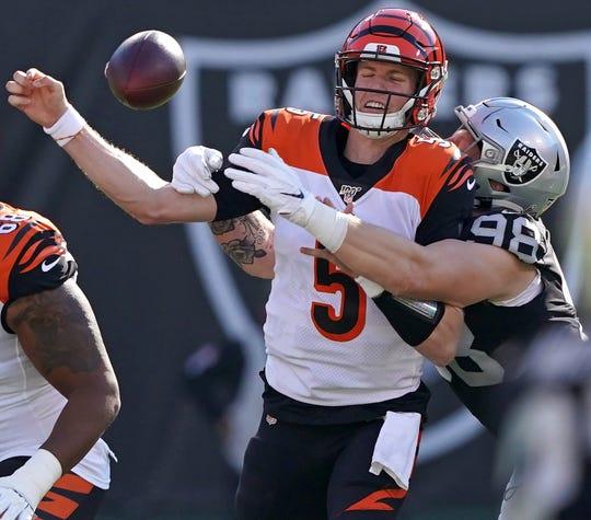 Oakland Raiders defensive end Maxx Crosby (98) forces a fumble by Cincinnati Bengals quarterback Ryan Finley.