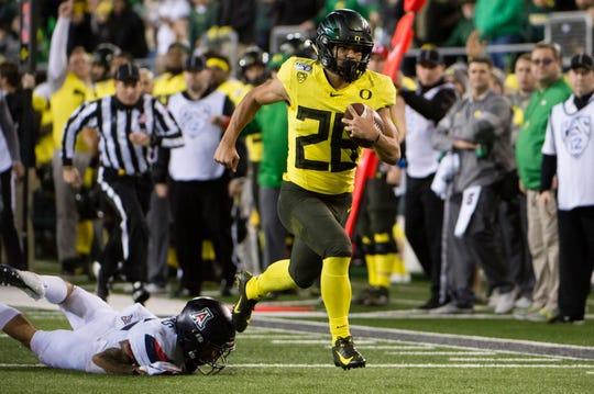 Oregon running back Travis Dye breaks away from an Arizona defender for a touchdown during the second half at Autzen Stadium.