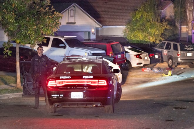 Officer Clapper waits in the street as Fresno Police investigate a shooting in the 5300 block of East Lamona Avenue on Nov 18, 2019. The shooting happened about 6p.m. in east-central Fresno and left four dead and six wounded during a gathering of about 35 people to watch football in the backyard.