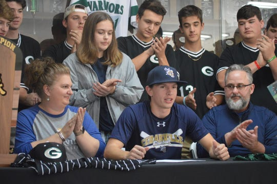 Grace Christian's Jimmy Miller (center) celebrates with family, friends and teammates after signing with Cedarville University Tuesday.