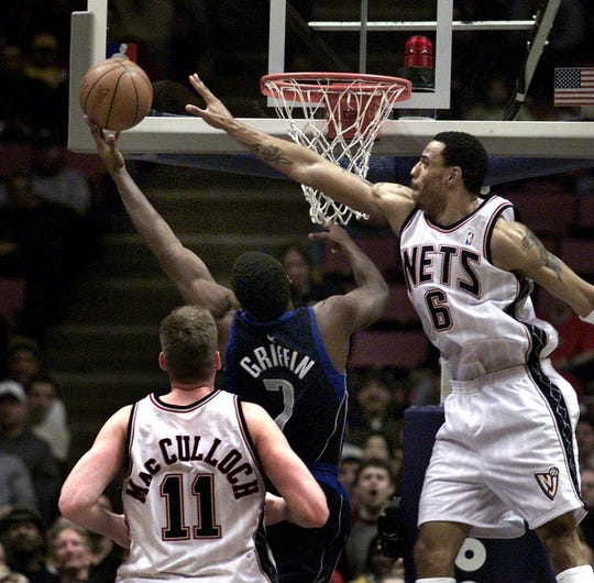 Playing for the Dallas Mavericks, Adrian Griffin (#7) goes up for a shot against the Nets in 2002.