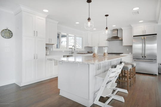 The high-end kitchen offers stainless steel appliances and white custom cabinetry.