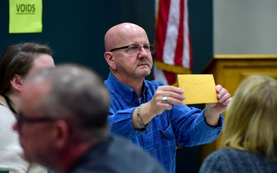John Warwick of Binghamton holds up an envelope containing a ballot during the absentee ballot count to decide the Broome County District Attorney race between Mike Korchak and Paul Battisti, held in the Broome County Board of Elections office in Binghamton on Tuesday, November 19, 2019.