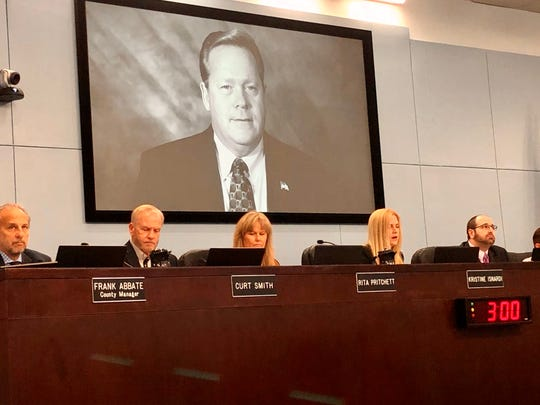 Former Brevard County Commissioner Andy Anderson's photo was displayed behind county commissioners, as his successor, Kristine Isnardi, paid tribute to him at the start of Tuesday's meeting.