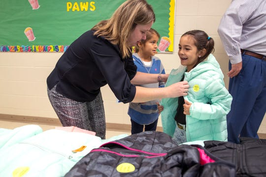 Morgan Davis, from left, helps Allen Elementary School students Arabella Caudillo, 6, and Hailey Perez, 6, pick out coats in the cafeteria on Tuesday, November 19, 2019. JCPenney and Fish For Life provided coats for all the students at the school.