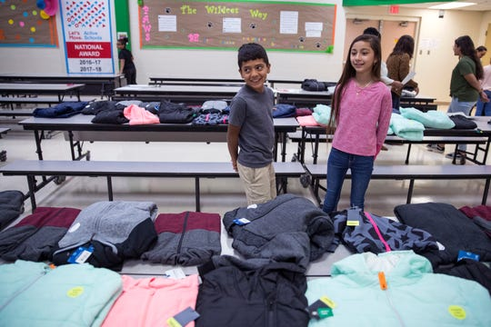 Allen Elementary School students Eric Suarez, left, 10, and Ameriah Garcia, 10, pick out coats in the cafeteria on Tuesday, November 19, 2019. JCPenney and Fish For Life provided coats for all the students at the school.