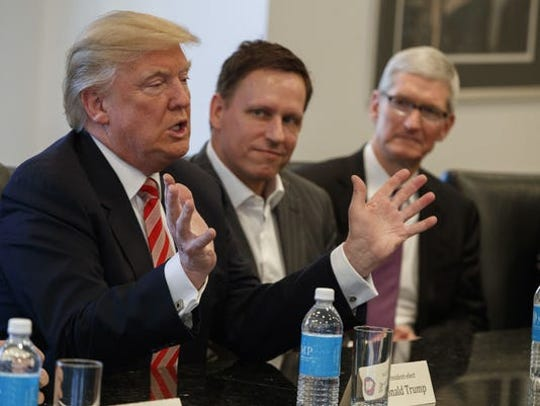 Apple CEO Tim Cook, right, and PayPal founder Peter Thiel, center, listen as Donald Trump speaks during a meeting with technology leaders on Dec. 14, 2016, at Trump Tower in New York.