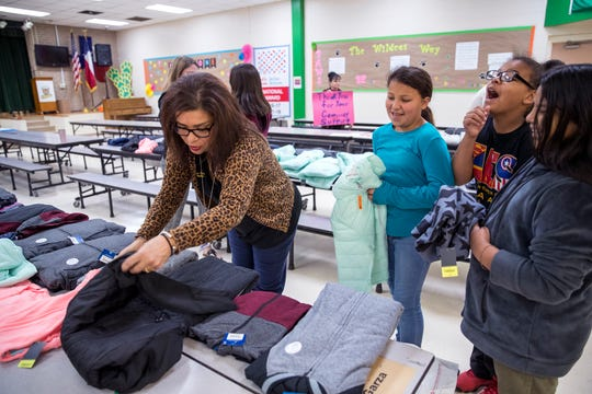 Judy Gonzalez-Rodriguez, from left,  helps Fifth-graders at Allen Elementary School Raine Morin, 10, Jeremiah Hernandez, 10, and Ariel Fuentes, 10 pick out coats in the cafeteria on Tuesday, November 19, 2019. JCPenney and Fish For Life provided coats for all the students at the school.