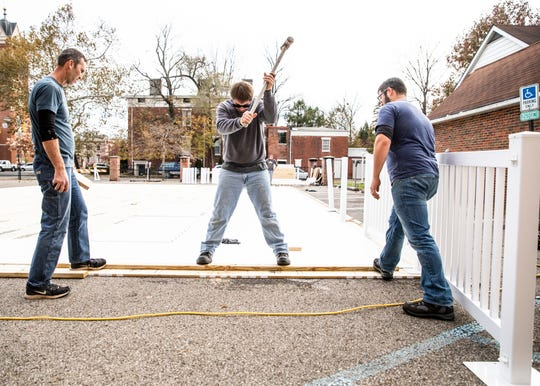 Clancy Spano, middle, uses a sledgehammer to move pieces of the ice before it is all fixed into position at the soon to be ice rink in Downtown Chillicothe.