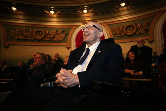 Hamilton County Commissioner Todd Portune smiles while listening to remarks as friends, politicians, community leaders and the public gathered to tribute Hamilton County Todd Portune, who will be retiring at the end of year, Monday, Nov. 18, 2019, at Hamilton County Memorial Hall.