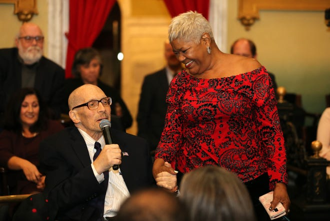 Hamilton County Commissioner Todd Portune and chief of Staff Victoria Parks hold hands as friends, politicians, community leaders and the public gathered in a tribute to Portune on Nov. 18, 2019, at Memorial Hall.