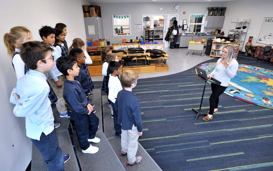 Pre-K through second-grade general music teacher Judy Pagryzinsky works with students practicing for a holiday concert in the new general music room.