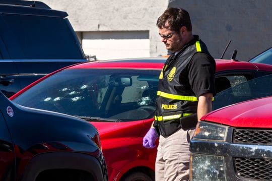 A member of the Oklahoma State Bureau of Investigation works the scene of a fatal shooting in the parking lot of a Walmart in Duncan, Okla., on Monday.