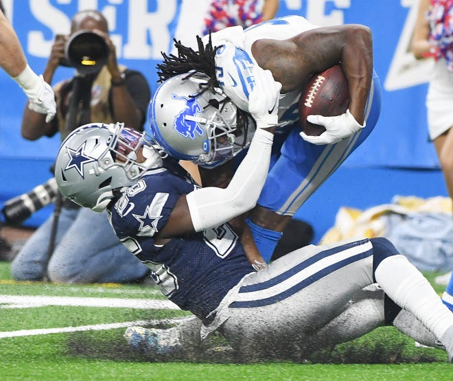 Cowboys' Xavier Woods brings down Lions' Bo Scarbrough in the second quarter on Sunday, which marked Detroit's sixth loss in seven games.