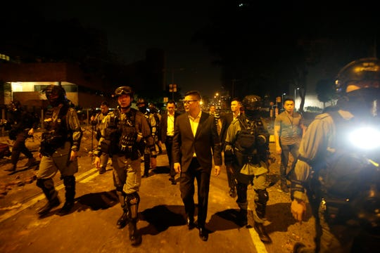 Chris Tang, center, the newly sworn-in Hong Kong police commissioner, walks with riot police near Hong Kong Polytechnic University in Hong Kong, Tuesday, Nov. 19, 2019.