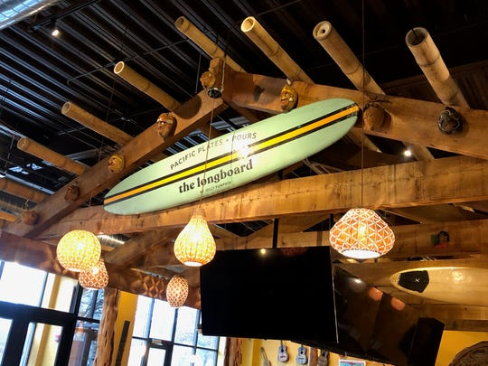 A surfboard hangs above the bar at Longboard, which serves Jolly Pumpkin and North Peak beers as well as tropical drinks.
