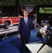 Chrysler Vice President Glenn E. White, who was a Plymouth Division general manager, stands with a racing engine in an undated photo.