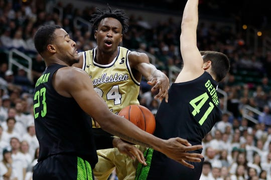 Charleston Southern guard Phlandrous Fleming Jr. (24) is defended by Michigan State forward Xavier Tillman (23) and guard Conner George (41) during the first half on Monday.