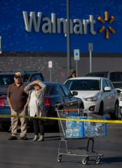 Shoppers look to the scene of a fatal shooting in the parking lot of a Walmart in Duncan, Okla., on Monday, Nov. 18, 2019.