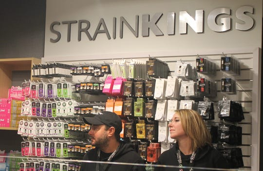 Two individuals watch on Tuesday, Nov. 19, 2019, inside Ann  Arbor retailer Exclusive Brands as the Marijuana Regulatory Agency gave the first recreational marijuana licenses to the business.