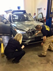 In this photo provided by the National Transportation Safety Board, investigators examine a driverless Uber SUV that fatally struck a woman in Tempe, Ariz.