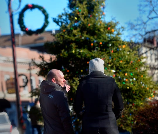 """Durham Town Administrator Todd Selig, left, speaks to an unidentified woman in front of a decorated tree on public land, in Durham, N.H. After concerns in 2018 that the tree-lighting ceremony at a park in Durham was too focused on Christmas, and a decision to deny a menorah to be displayed next to the tree, town councilors came up with the idea of a celebration that pays tribute to winter called """"Frost Fest."""""""