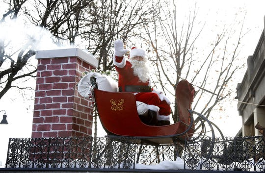 Santa waves to children during the 2016 Downtown Elmira Holiday Parade.