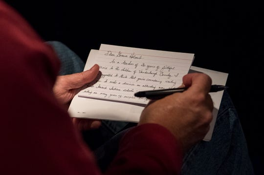 North High School French teacher Van Ruckman writes a letter to Gov. Holcomb on the bus ride to the Indiana Statehouse to participate in Red for Ed Action Day in Indianapolis, Ind., Tuesday morning, Nov. 19, 2019.