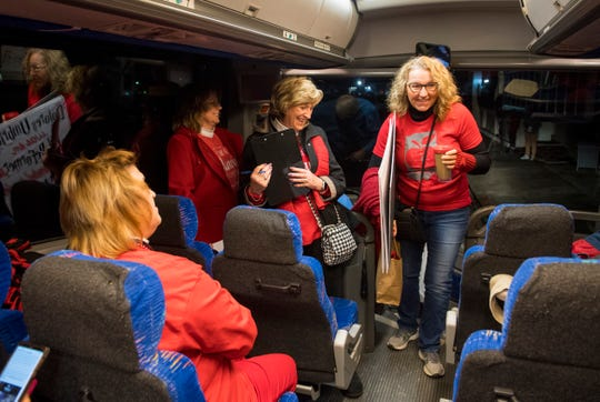 Third grade teacher at McCutchanville Elementary School Jane Elgin, right, boards a bus headed to the Indiana Statehouse to participate in Red for Ed Action Day Tuesday morning, Nov. 19, 2019.