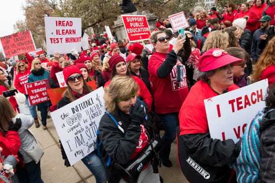 Protesters for education reform walk down in front of the Statehouse in downtown Indianapolis, Ind., while participating in the Red for Ed Action Day rally Tuesday afternoon, Nov. 19, 2019.