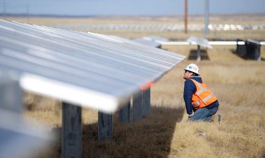 Kenny Stewart, a DEPCOM field engineer, looks at the solar panels in the Rawhide Flats Solar site in Wellington, Colo. on Tuesday, Nov. 19, 2019.