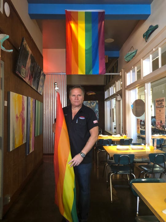 Chris Blauvelt, owner of The Standard, holds a pride flag at his restaurant on Monday. Blauvelt said his landlord has asked him to stop flying the flag due to safety concerns.