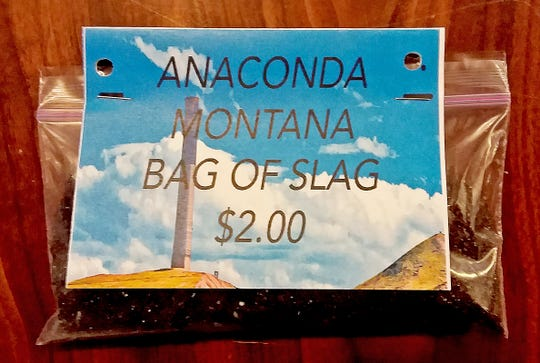 """In this undated photo provided by the Anaconda Chamber of Commerce, a bag of mining slag that was available for purchase as a souvenir at the Anaconda Chamber is seen. Environmental regulators have put a halt to a Montana business association's sale of sandwich bags of mining waste advertised as a """"Bag O'Slag."""" Environmental Protection Agency officials overseeing the Superfund site cleanup of pollution from nearly a century of smelting operations in Anaconda came across the potentially toxic tchotchkes for sale by the city's chamber of commerce. The slag, a byproduct of smelting copper, contains small amounts of arsenic and lead. (Mary Johnston/Anaconda Chamber of Commerce via AP)"""