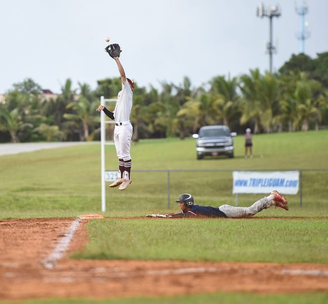 In this file photo, Father Duenas third baseman Aiden Lizama leaps to make a catch on a steal by Simon Sanchez player Javier Concepcion during an IIAAG baseball game  Nov. 18, 2019 at Okkodo High School, Dededo.