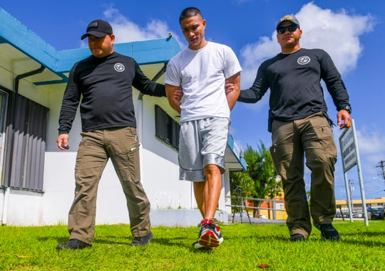 Department of Corrections detainee Patrick Hernandez, center, is escorted by officers of the Guam Police Department's Criminal Investigation Division from GPD's Hagåtña Precinct after his recapture on Tuesday, Nov. 19, 2019. Hernandez was located by law enforcement officers in the village of Maina after escaping from the Dept. of Corrections detention facility in Hagåtña, earlier the same morning.
