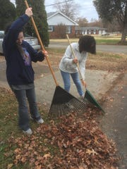 Kaleigh Musgrave, left, and Dejhia Chester rake leaves in the neighborhood beside Henderson County High School Tuesday.