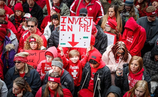 Teachers and their supporters wave signs during the Red for Ed Action Day at the Indiana Statehouse on Tuesday, Nov. 19, 2019.