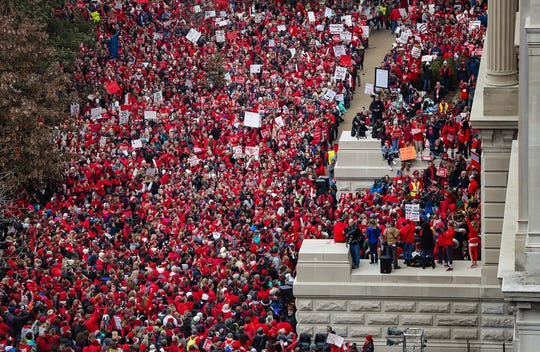 Thousands rally on the south lawn of the Indiana Statehouse on Red for Ed Action Day in Indianapolis on Tuesday, Nov. 19, 2019. The rally was organized by the Indiana State Teachers Association and other labor groups to urge legislators to increase school funding and teacher salaries.