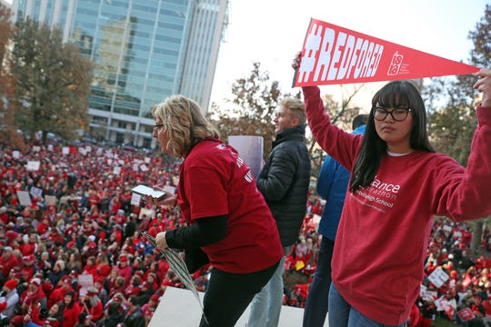 Teachers cheer on the crowd at the Red For Ed rally from the top of the steps of the Indiana Statehouse on Tuesday, Nov. 19, 2019.