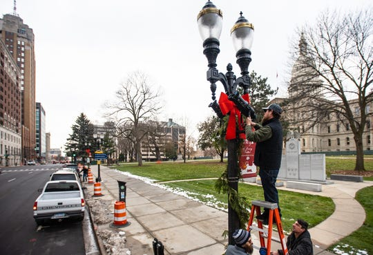 Jon Babcock, top, Brandon Cook, and John Miller, right, of All Star Media  in Lansing mount jobo lights Tuesday, Nov. 19, 2019, that will project snowflakes and the Silver Bells in the City logo onto City Hall this Friday evening, during the 35th annual Silver Bells in the City event.