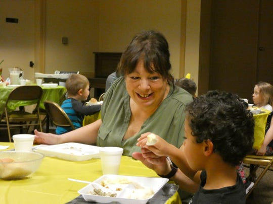 Colleen Miller, a teacher at Epworth Preschool and Day Care, helps feed kids a Thanksgiving meal last year.