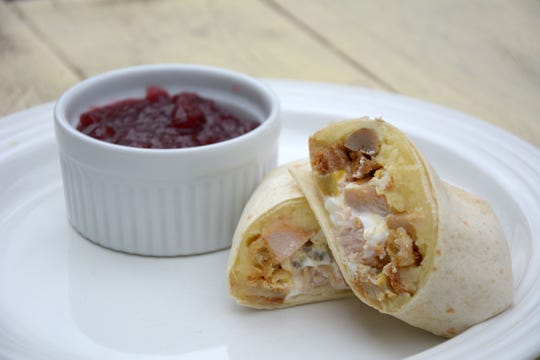 Various Thanksgiving leftovers are stuffed into a flour tortilla for a hearty breakfast after the holiday is over.