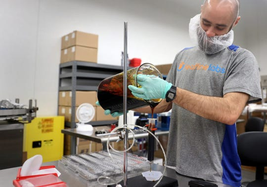 LeafLine Labs employee Antonio Ryan pours cannabis oil into a syringe in the packaging room of the company's headquarters in Cottage Grove, Minn., April 18, 2019. The 42,000-square-foot indoor cultivation and production facility is used to grow marijuana for medical use. LeafLine Labs director of operations Megan Gaulke says the oil is the base for most of LeafLine Labs' products. Medical marijuana is not currently legal in Wisconsin.